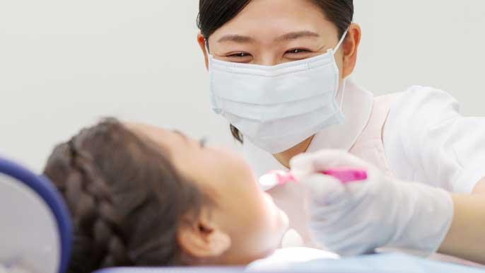 歯医者でのフッ素塗布治療を受けている女の子