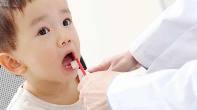 歯医者でのフッ素塗布治療を受けている不安そうな顔をして男の子